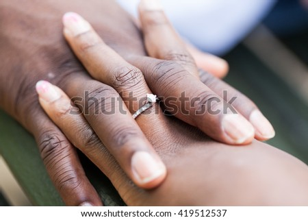 Hands of an nigerian couple. She is wearing an engagement ring. High resolution and details