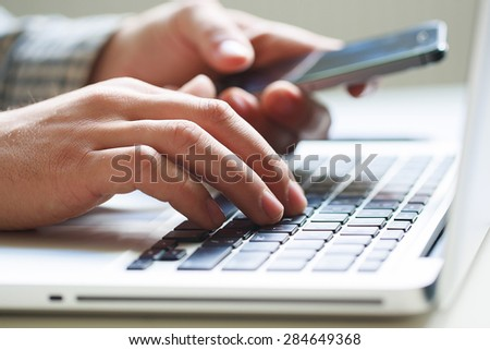 hands of an office worker on the keyboard, holding cellphone