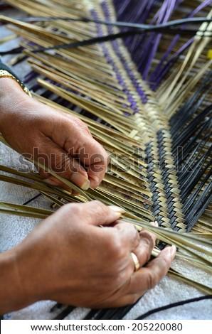 Hands of an old Maori woman weaving a traditional Maori woven artwork. - stock photo