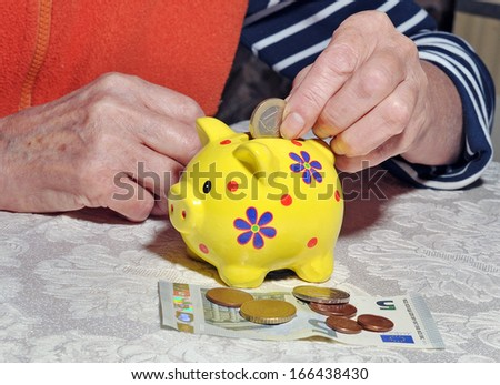 Hands of an old woman put a coin in a piggy bank - stock photo