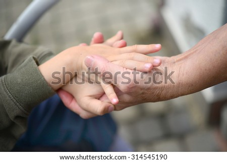 hands of an older woman and the child