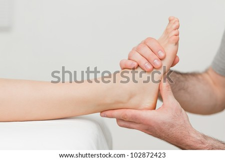 Hands of an osteopath massaging a foot in a room