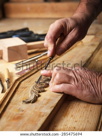 Hands of an senior carpenter restoring old furniture - stock photo