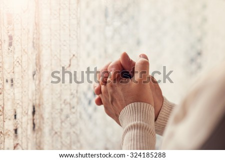 Hands of an unrecognizable woman standing by the window and praying - stock photo