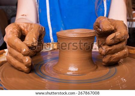 hands of artisan on pottery wheel - stock photo