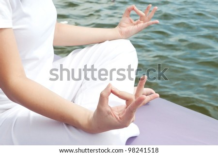 Hands of attractive young asian woman practicing yoga meditation at sunrise by the ocean - stock photo