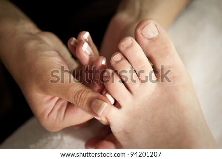 hands of beauty therapist doing foot massage during pedicure