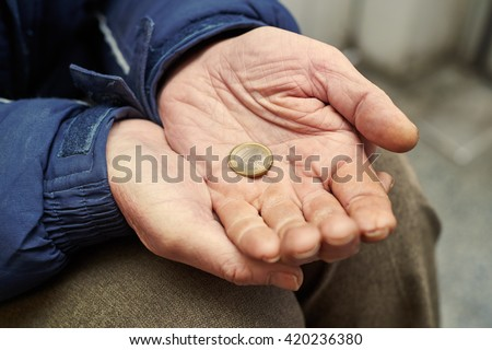 hands of beggar with one euro coin begging for money  - stock photo
