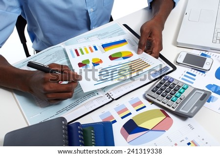Hands of black businessman with calculator. Accounting - stock photo