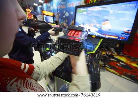 Hands of boys playing video games, they hold joystick in front of the monitor - stock photo