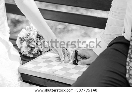 Hands of bride and groom are playing chess. Bridal bouquet on a green bench. Bride and groom like a king and queen. Beautiful wedding romantic background. Black and white photo. - stock photo