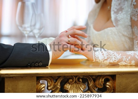 Hands of bride and groom at the wedding. - stock photo