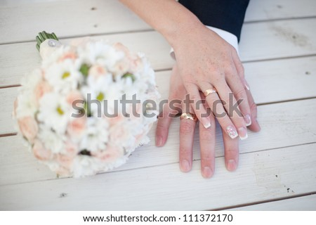 Hands of bride and groom with bouquet - stock photo