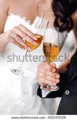 Hands of bride and groom with glasses of champagne  - stock photo