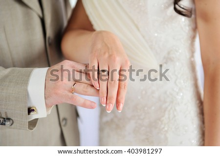 hands of bride and groom with gold rings on wedding