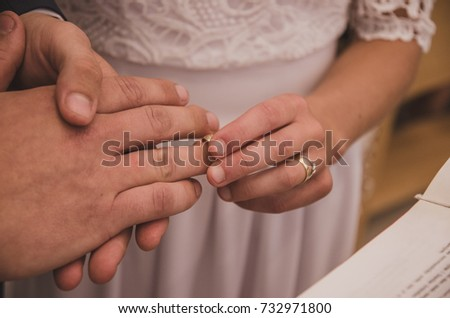 Hands of bride and groom with ring, wedding ceremony outdoor.
