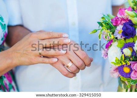 hands of bride and groom with rings and wedding bouquet. - stock photo