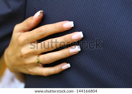 Hands of bride with wedding ring embracing groom - stock photo