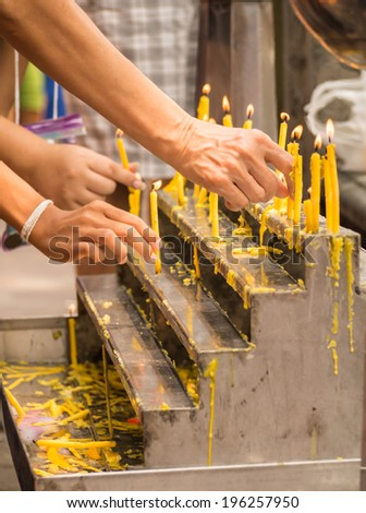 Hands of Buddhists lighting up the candles on altar to pay their respect to Lord Buddha in Buddhist temple, Thailand - stock photo