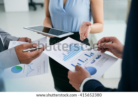 Hands of business executives discussing financial reports - stock photo
