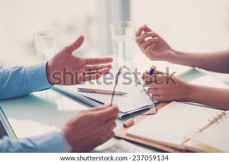 Hands of business people discussing annual report - stock photo