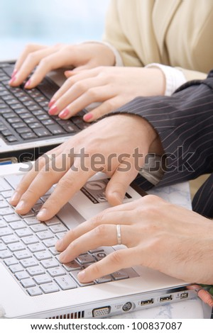 Hands of business people on notebook keyboard