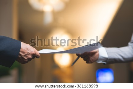Hands of business people passing document - stock photo