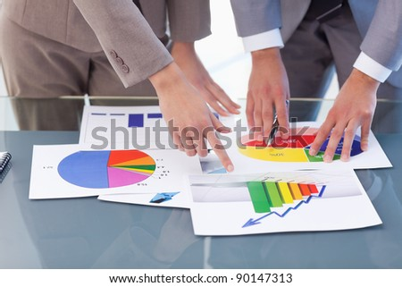 Hands of business people studying statistics in a meeting room - stock photo