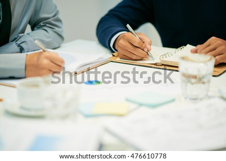 Hands of business people taking notes during discussion