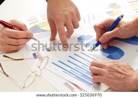 Hands of business people working with graphs. Teamwork.