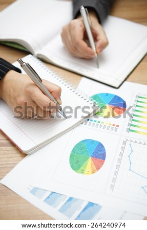 Hands of business people  writing down tasks to do after brainstorming - stock photo