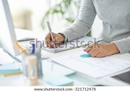Hands of business person making notes in notepad - stock photo