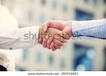 Hands of businessman and businesswoman shaking hands, while in the background looms office building.