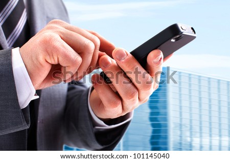 Hands of businessman calling by phone. On abstract urban background. - stock photo