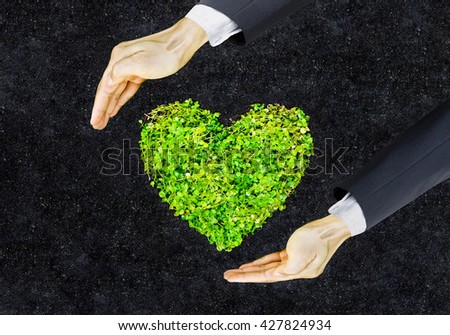 hands of businessman holding green heart shaped tree / business with environmental concern / csr / Go green / Corporate Social Responsibility / Sustainable development - stock photo