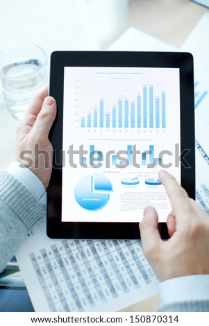 Hands of businessman holding touchpad with electronic document - stock photo