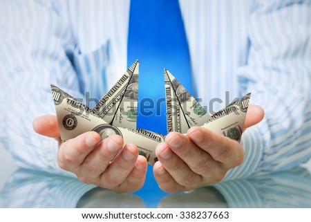 Hands of businessman holding with care dollar banknote ship
