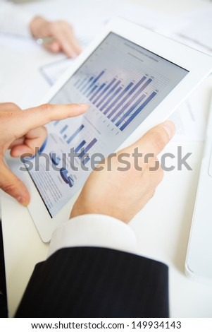 Hands of businessman pointing at touchpad with electronic document
