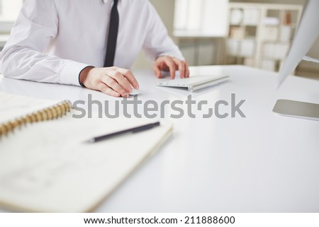 Hands of businessman sitting in office and typing - stock photo