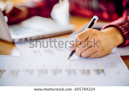 Hands of Businessman working on Laptop Computer with Data Charts