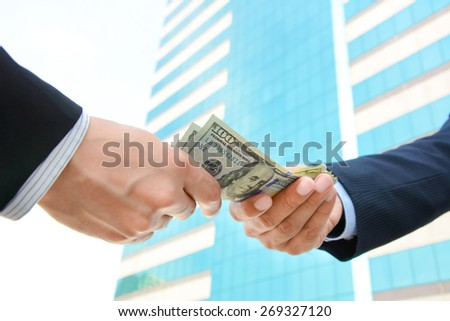 Hands of businessmen passing money - stock photo