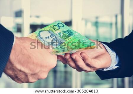 Hands of businessmen passing money, Australia dollar (AUD) banknotes - stock photo