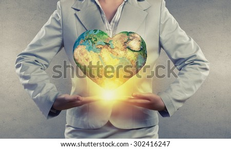 Hands of businesswoman holding earth planet. Elements of this image are furnished by NASA