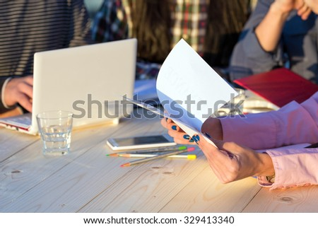 Hands of Businesswoman Holding Paper Prints of Presentation and Discussing with Partners Sitting around Wood Table with Laptop Pencils Telephone Glass of Water and Notepads - stock photo