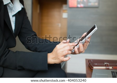 Hands of businesswoman playing mobile phone in the hotel lobby.