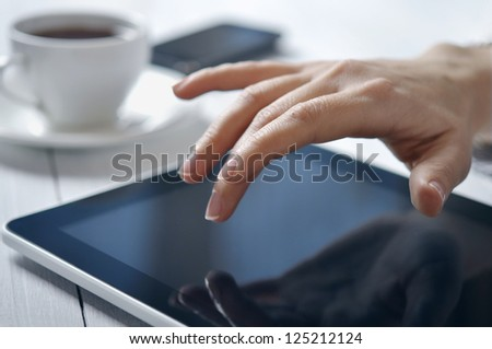 Hands of businesswoman using tablet PC at office - stock photo