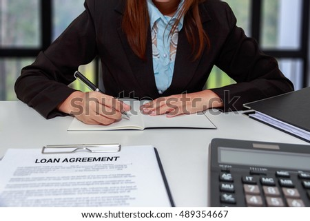 Hands of businesswoman writing on notebook with calculator and loan agreement at office desk