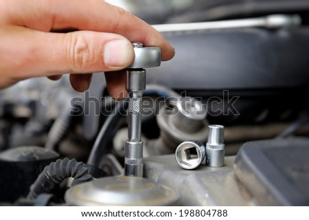 Hands of car mechanic in auto repair service - stock photo