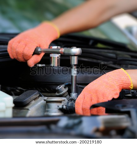 Hands of car mechanic in auto repair service