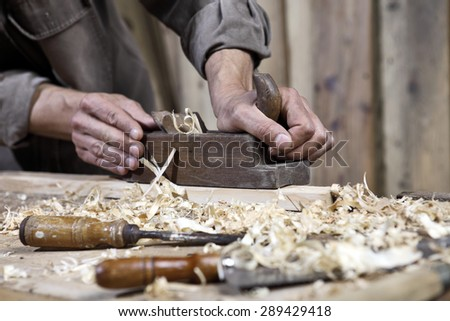 hands of carpenter plane on the workbench in carpentry - stock photo